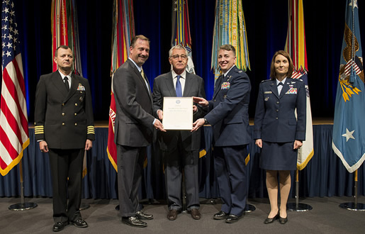 DTRA/SCC-WMD Director Ken Myers and USAF Col. John Cinnamon accept the Joint Meritorious Unit Award from Secretary of Defense Chuck Hagel (center) for the One Team role in the mission to destroy Syria's chemical weapons at sea aboard the M/V Cape Ray, along with USN Capt. Scott Evertson (left) and USAF Lt. Col. Jannell Macaulay (right).