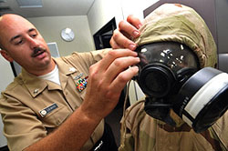 A U.S. Navy chemical/biological defense officer helps a sailor don a joint-service lightweight integrated suit technology chemical-protective ensemble during a chemical, biological, radiological and nuclear defense training course. (U.S. Navy photo)